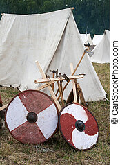 Two shield and some axes near tents Historical...