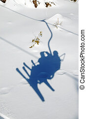 Ski chairlift with skiers shadow on snow