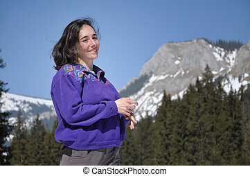 Portrait of a young woman at winter in the mountains