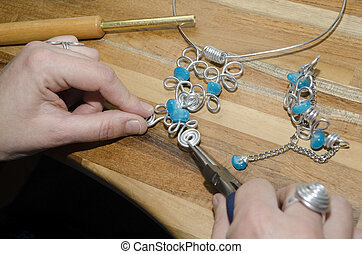 womans hands creating a fashion jewelery with silver metal...