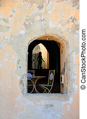 cafe with old vintage chairs in the window of the old wall