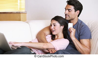 Couple lying on a couch while making shopping online in...