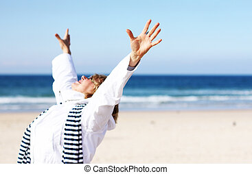 Senior Woman With Arms Outstretched On Winter Beach Focus on...