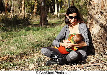 beautiful young mother breastfeeding a sunny spring day
