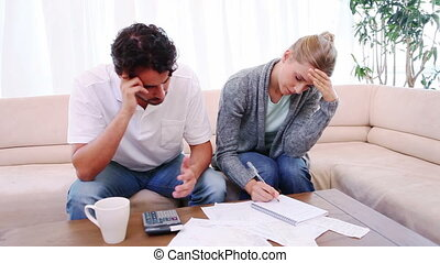 Couple checking their bills in their living room
