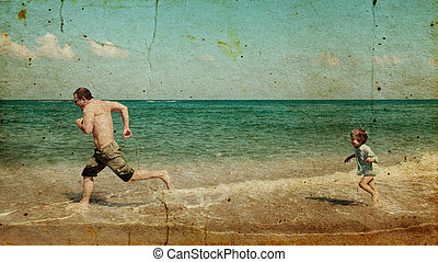 father and son playing together on the beach Photo in old...