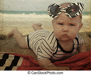 fashion baby on seaside. Photo in old color image style.