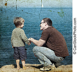Father and son at sea watching the sunset Photo in old image...