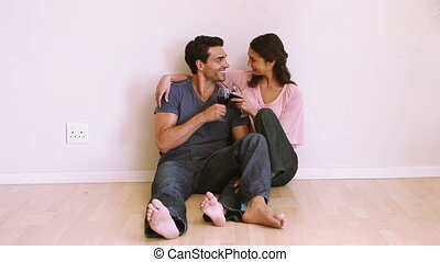 Smiling couple clinking glasses in an empty room