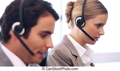 Call centre agent talking while using her headset in a...