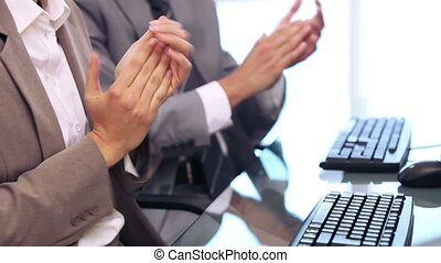 Business people applauding while sitting in a bright office