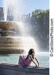 Girl by waterfountain - Unidentifiable girl sitting by edge...