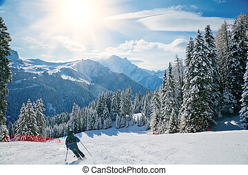 Ski slope - Skier going down the slope at Val Di Fassa ski...