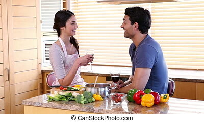 Smiling couple drinking glasses of wine in a kitchen