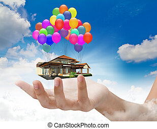 A house lifted by Balloons on hand