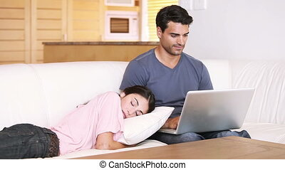 Young man using his laptop while sitting next to his girlfriend