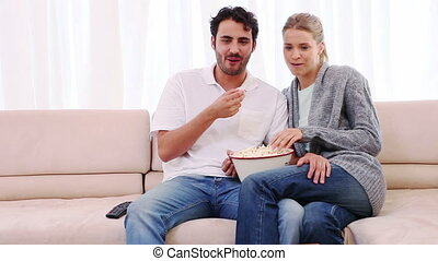 Couple eating popcorn while watching a movie in their living...