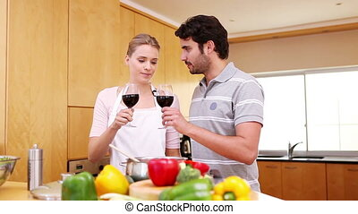 Couple clinking their glasses of red wine in the kitchen