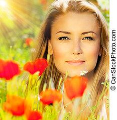 Closeup on beautiful woman face, female enjoying flower...