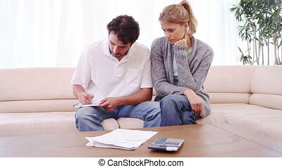 Young woman looking at her boyfriend checking the bills