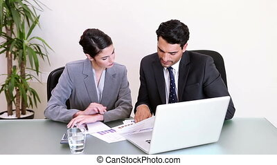 Two business people working while sitting at a desk