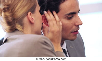 Businesswoman telling a secret to her colleague in a bright...