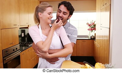 Couple standing upright together in the kitchen