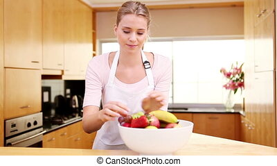 Young woman placing a bowl of fruit on the worktop in the...