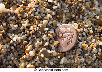 old greek copper coin in sea sand