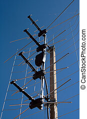 aerial TV antenna on rooftop over blue cloudless sky