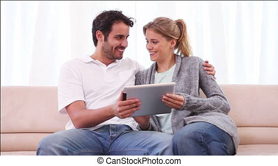 Smiling couple using a tablet computer in the living room