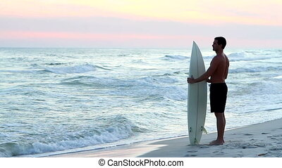 Surfer At Twilight - Male surfer holding his surfboard...