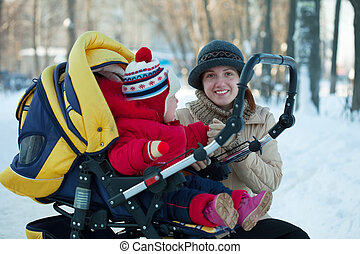 Woman  with child in pram  at wintery park