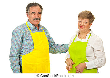 Happy mature couple with aprons