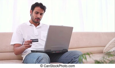 Man using his laptop and a credit card in his living room