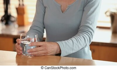 Woman lifts a glass of water off a table and takes a drink