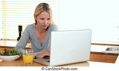 Woman with a laptop takes a drink of orange juice - Woman...
