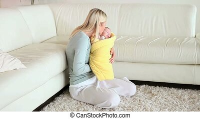Woman kissing and rocking a baby in her arms