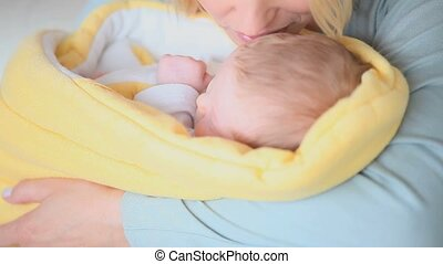 Woman kissing a child on the forehead while he sleeps