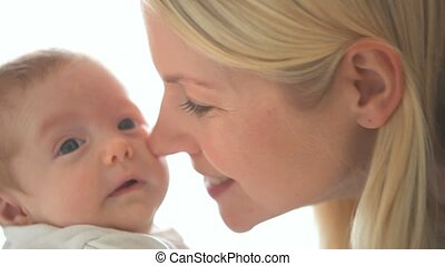 Woman holding a baby and kisses him