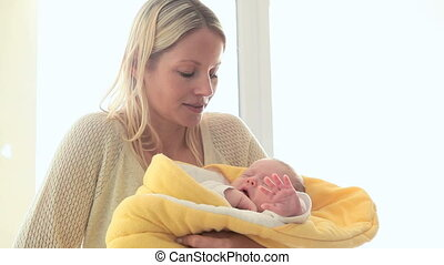 Woman smiling while holding a child in a yellow blanket -...