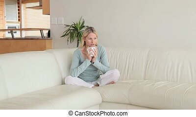 Woman holding a hot coffee sitting in a living room