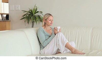 Woman sitting on a sofa drinking coffee - Woman drinking...