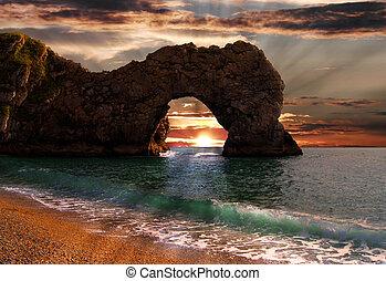 Durdle Door Arch, Dorset - Sunrise through Durdle Door sea...
