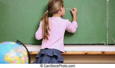 Blonde girl writing on the blackboard in the classroom