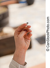 Hand with cigarette - Person smoking a cigarette rolling...