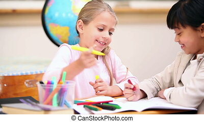 Smiling pupils coloring in the classroom