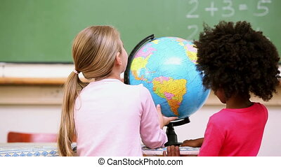 Friends looking at a globe in the classroom
