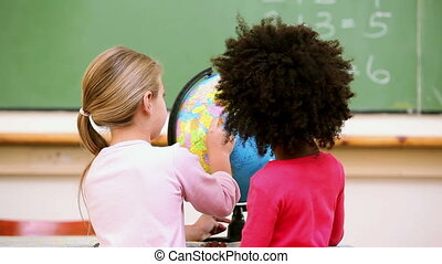 Cute pupils looking at a globe in the classroom