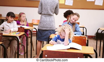 Teacher handing out papers in the classroom